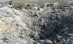Des Syriens inspectent un cratère après un raid de la coalition, dans la ville de Harem, en Syrie, le 19 novembre 2014