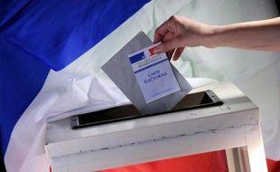 Une personne insère un bulletin de vote dans un urne