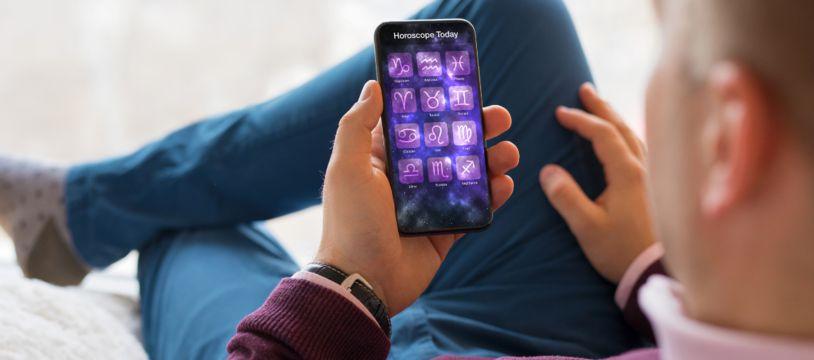 (Illustration) Un homme consulte son horoscope sur son téléphone