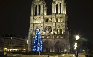 Un grand sapin de noël devant Notre-Dame de Paris.