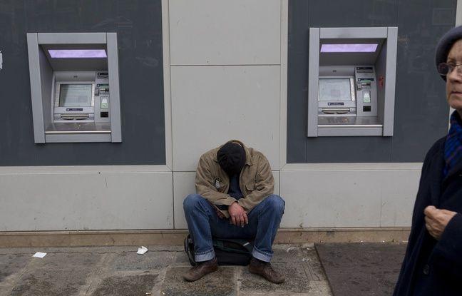 Paris le 30 octobre 2012. Illustration SDF Sans Domicile Fixe devant un distributeur de billets de banque.