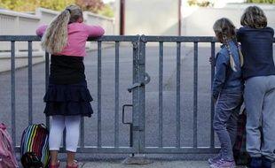 Des enfants attendent devant les grilles fermées de Ganzeville en Normandie, le 10 septembre 2014