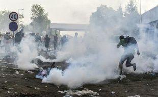 Des réfugiés courent pour se protéger des gaz lacrymogènes à la frontière serbo-croate près de la ville de Horgos, le 16 septembre 2015