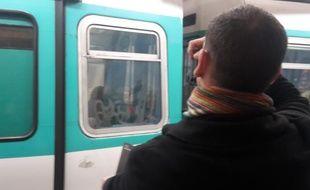 Le tagueur, Azyle, devant un des ultimes vestiges à l'acide sur la vitre du métro.