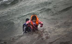 A man carries a child as they try to reach a shore after falling into the sea while disembarking from a dinghy on which they crossed a part of the Aegean sea with other refugees and migrants, from Turkey to the Greek island of Lesbos, on Sunday, Jan. 3, 2016. More than a million people reached Europe in 2015 in the continent's largest refugee influx since the end of World War II. Nearly 3,800 people are estimated to have drowned in the Mediterranean last year, making the journey to Greece or Italy in unseaworthy vessels packed far beyond capacity. (AP Photo/Santi Palacios)/XYK112/4712433725/1601031755