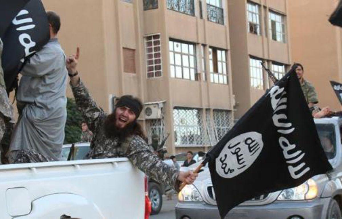 Image extraite du média jihadiste Al-Baraka news, le 11 juin 2014, montrant des militants de l'EI et leur drapeau noir dans la ville syrienne de Raga – - Welayat Raqa