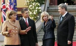 La chancelière Angela Merkel (G) et son mari Joachim Sauer accueillentle Premier ministre canadien Stephen Harper (D) et sa femme Laureen, avant l'ouverture du sommet par un dîner à Hohen Luckow, le 6 juin 2007.