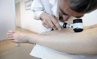 Un dermatologue qui vérifie qu'une patiente n'a pas un mélanome.