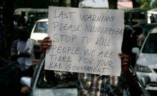 """Une pancarte sur laquelle on peut lire """"Dernier avertissement Nkurunziza, cessez de tuer des gens, nous en avons assez de votre mauvais gouvernement"""", brandie par un manifestant lors des funérailles d'un journaliste à Bujumbura le 20 octobre 2015"""