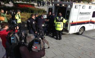 Ambulanciers et policiers s'occupent d'une personne blessée par des tirs au Mémorial de la Guerre à Ottawa (Canada) le 22 octobre 2014