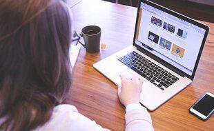 une étudiante devant son écran d'ordinateur pour accéder à des cours en ligne.