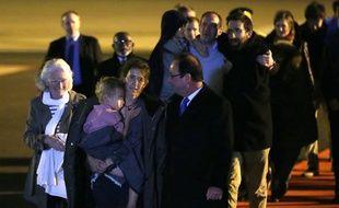Le président Francois Hollande parle avec  Albane Moulin-Fournier, qui porte l'un de ses enfants, devant les autres membres de la fammile Moulin-Fournier, qui viennent d'arriver de Yaoundé à Orly, le 20 avril 2013.