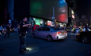 Un policier régule le trafic pendant une coupure de courant à Times Square, New York, le 13 juillet 2019.