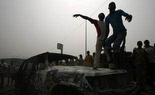 Des étudiants pro-Gbagbo sur un véhicule des Nations unies brûlé le 13 janvier 2011, à Abidjan, en Côte d'Ivoire.