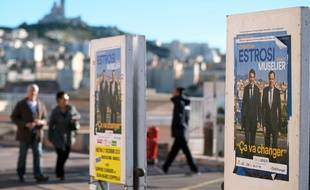 People walk by electoral posters for the upcoming regional elections in Marseille on November 30, 2015. AFP PHOTO / BORIS HORVAT