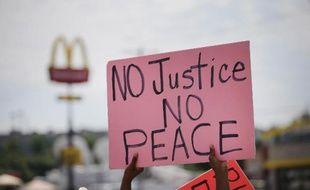 """""""Sans justice, pas de paix"""" peut-on lire sur la pancarte d'une manifestante à Ferguson (Missouri), le 19 août 2014"""
