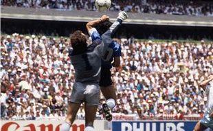 L'Argentin Diego Maradona (maillot bleu) saute le poing en l'air pour reprendre le ballon lors d'une demi-finale de la Coupe du monde 1986 face à l'Angleterre