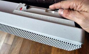 Une personne augmente la température de son radiateur