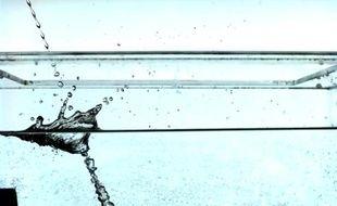 Image au ralenti du flux d'un liquide rencontrant la surface de l'eau.
