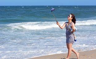 Une femme prend un selfie sur la plage en Australie.