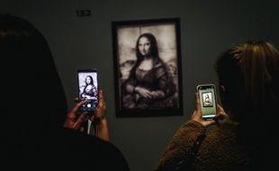 """Des visiteurs prennent en photo le premier dessin de """"La Joconde"""" par Léonard de Vinci, révélé par la réflectographie infrarouge"""