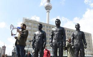 Le sculpteur italien Davide Dormino (G) s'exprime lors de l'inauguration de son monument en bronze représentant Edward Snowden, Julian Assange et Chelsea Manning , le 1er mai 2015 à Berlin.