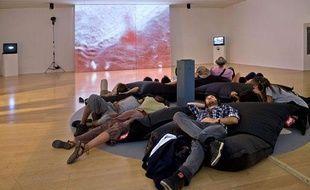 Les visiteurs écoutent, grâce à un casque, une danse narrée par Trisha Brown au Mac de Lyon.