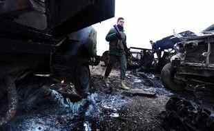 Un combattant Peshmerga au milieu carcasses de voitures après un attentat du groupe Etat islamique à Kesarej en Irak, le 18 décembre 2014