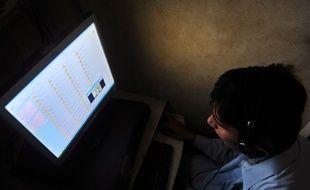 Un homme devant un ordinateur (image d'illustration)