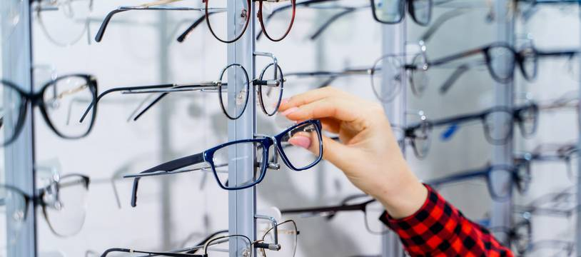 Woman choosing new pair of spectacles in opticians store. Optics. Ophthalmology.