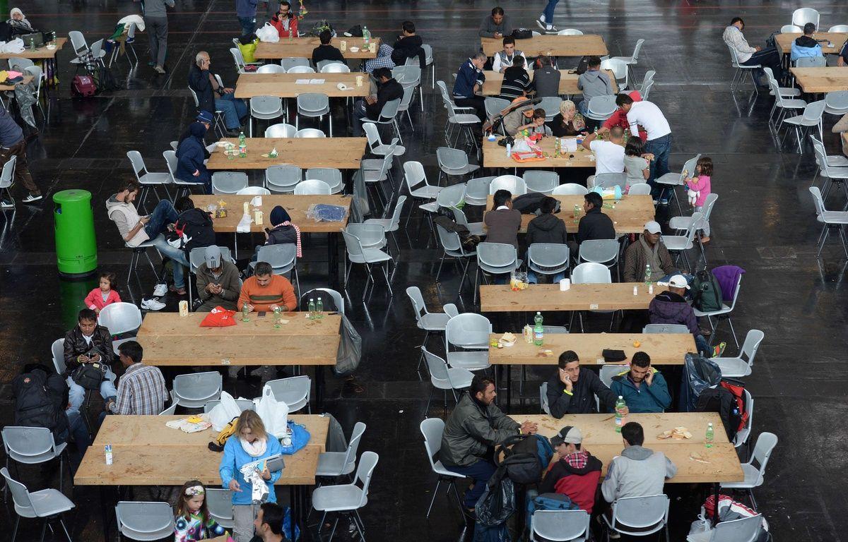 Des réfugiés installés à table dans un hall à Munich, en Allemagne le 7 septembre 2015. – AFP