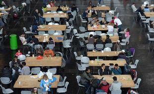 Des réfugiés installés à table dans un hall à Munich, en Allemagne le 7 septembre 2015.