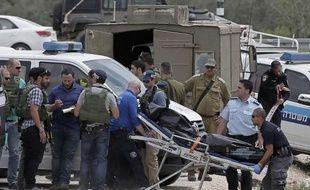 Les forces de sécurité israéliennes transportent le 8 avril 2015 le corps d'un Palestinien à Sinjil (Cisjordanie), responsable de l'agression de deux soldats israéliens