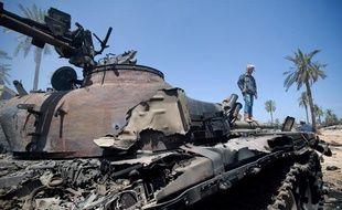 Un rebelle à côté de la carcasse d'un tank de l'armée loyale à Mouammar Kadhafi à Misrata, le 19 avril 2011.