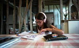 Jeune fille (agee de 10 ans) en vacances, ecoutant de la musique sur son lecteur MP3. Gers, France, 7 Aout 2017.