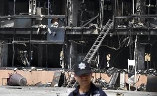 Un policier monte la garde devant le siège incendié par des manifestants du gouvernent de l'Etat de Guerrero, à Chilpancingo, le 14 octobre 2014