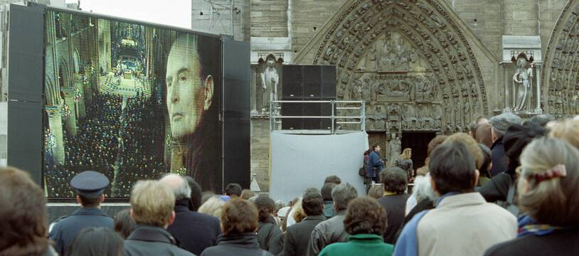 Les gens suivent sur un écran géant installé sur la place devant la cathédrale Notre-Dame à Paris, la cérémonie religieuse en hommage à François Mitterrand, le 11 janvier 1996.