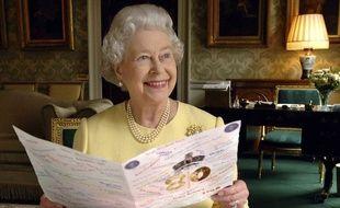 Le reine Elizabeth II lit une carte de vœux qui lui a été envoyée pour son 80e anniversaire à Buckingham Palace, le 20 avril 2006.