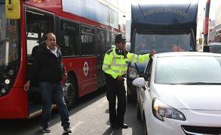 Un policier devant un bus à Londres (illustration).