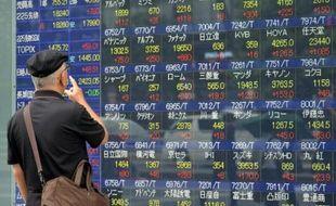 Un homme regarde un tableau d'indices boursiers, le 9 septembre 2015 à Tokyo