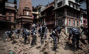 Des policiers népalais déblayent le 3 mai 2015 les débris laissés par le séisme sur la place Dunbar de Katmandou