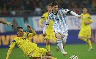 Le défenseur roumain Dragos Grigore tacle l'attaquant argentin Lionel Messi, lors du match amical Roumanie - Argentine (0-0), le 5 mars 2014 à Bucarest.