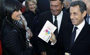 Nicolas Sarkozy se fait offrir un livre où est inscrit «Mince alors» lors de la visite d'un centre de tri des déchets près de Laval, en Mayenne, le 20 octobre 2011, au lendemain de l'accouchement de son épouse, Carla Bruni-Sarkozy.