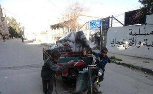 Des garçonnets poussent un véhicule dans une rue du camp de réfugiés palestiniens de Yarmouk, dans le sud de Damas, le 4 avril 2015