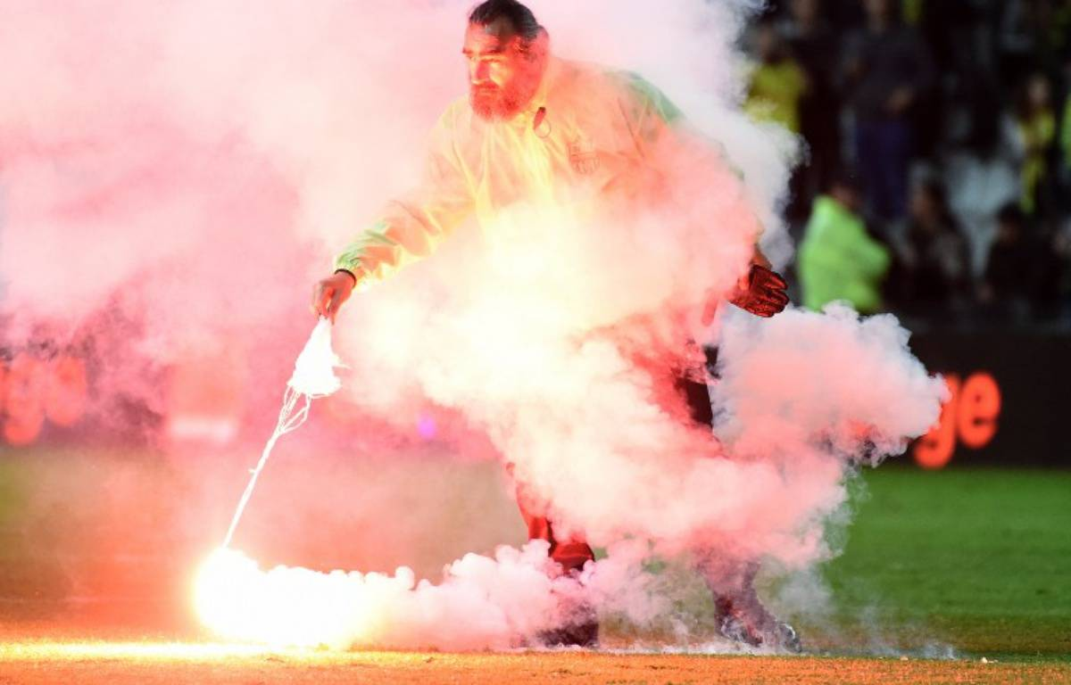 Un des fumigènes balancés sur la pelouse en fin de match. – JEAN-SEBASTIEN EVRARD / AFP