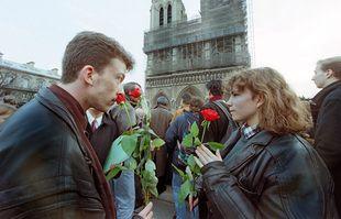 Les gens sont rassemblés devant la cathédrale Notre-Dame de Paris, le 11 janvier 1996, alors qu'un immense écran vidéo retransmet la messe solennelle célébrée à la mémoire de l'ancien président français François Mitterrand.