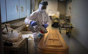 Un employé de morgue désinfecte un cercueil contenant le corps d'une personne décédée du COVID-19 avant des funérailles à la morgue Memora de Gérone, en Espagne, le jeudi 4 février 2021.