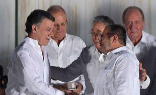 Le président colombien Juan Manuel Santos (à g.) et le chef des Farc Timochenko (à dr.) après la signature de l'accord, en présence du président cubain Raul Castro, à Carthagène, le 26 septembre 2016