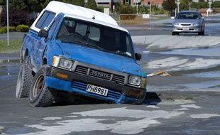Une voiture enfoncée dans la route, après le séisme qui a frappé la banlieue de Christchurch, le 23 décembre  2011.