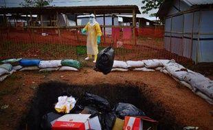 Un travailleur de Médecins sans frontières jette des affaires qui seront incinérées à Kailahun en Sierra Leone le 14 août 2014